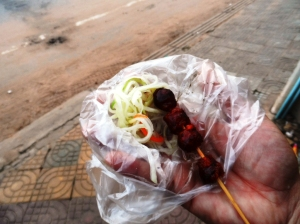 Chorizo like - skewer . Always with green papaya salad. But not as sour as Pinoy Atchara
