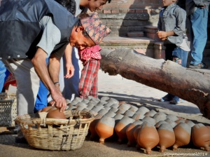 Nepalese Man , collecting his sun dried Clay Pots before sunset . Been doing this every day for years . These claypots are used to keep yogurts, a staple food of Nepalese.