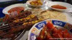 Kebabs with tomato salad sides. a stick o